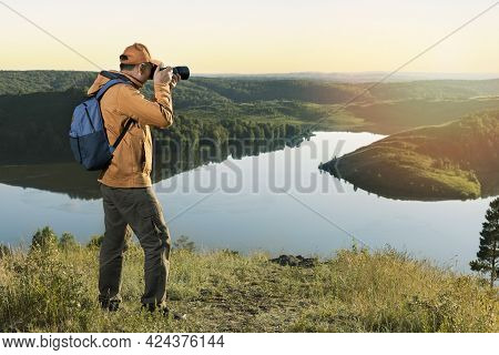 Man Hiker In A Vibrant Yellow Coat With A Backpack And Camera Taking Photo Of Sunset Mountains. Trav