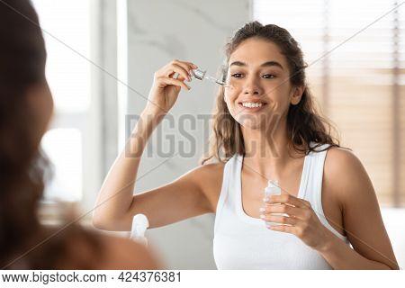Attractive Female Applying Serum On Face Moisturizing Skin In Bathroom
