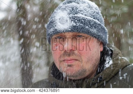 Portrait Of A Caucasian Man Walking Through A Forest In Winter In A Heavy Snowstorm.