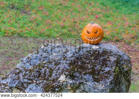 Scary Smiling Halloween Pumpkin With Nasty Face On A Stone. Big Scary Smiling Halloween Pumpkin With