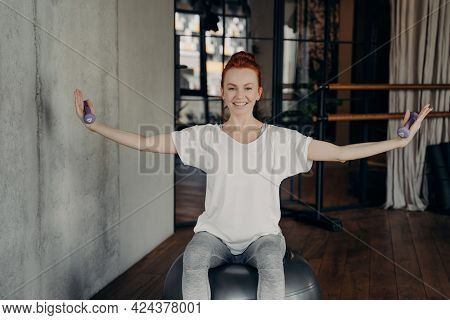 Redhead Joyful Female Fitness Instructor With Smile Exercising With Small Dumbbells On Silver Fitbal