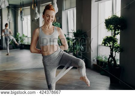 Slim Pretty Fitness Girl With Red Hair In Top Tank And Leggings Doing Exercise With Rubber Resistanc