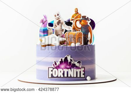 Birthday Cake For A Fan Of Online Computer Game Fortnite By Epic Games. Purple Cake On The White Bac