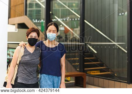 Happy Lesbian Couple In Protective Mask Embracing Each Other On Front Of Building
