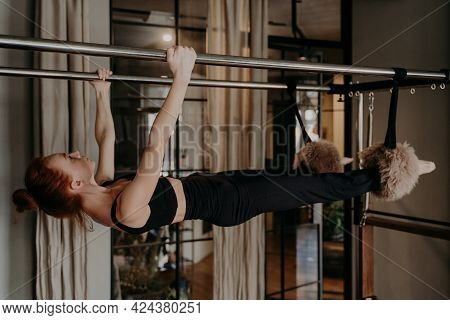 Side View Of Strong Healthy Pilates Woman With Athletic Body Exercising And Stretching While Hanging