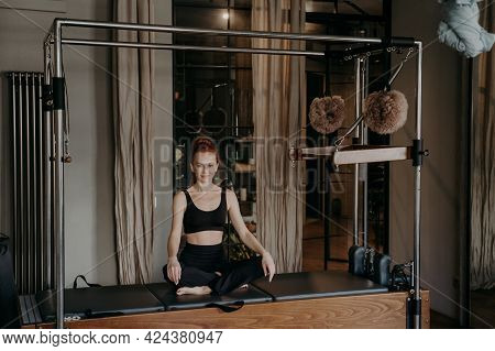 Beautiful Fit Woman Sitting In Very Relaxed Lotus Position On Top Of Trapeze Table Or Cadillac Refor