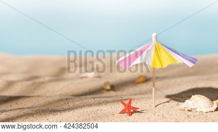 Sunshade Umbrella On A Sandy Beach With Seashells. Summer Vacation Concept.summer Background.