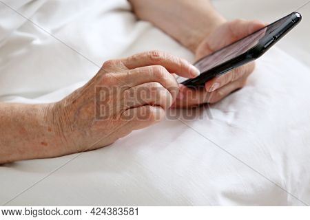 Elderly Woman With Smartphone Sitting In Bed, Mobile Phone In Wrinkled Female Hands Close Up. Concep