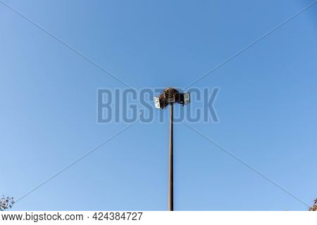 Light Tower With Birds Nest On Blue Background.