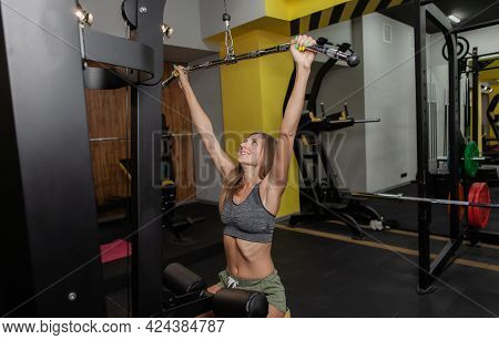 Fit Woman In Sportswear Exercise With Exercise Weight Machine In Gym. Attractive Girl Training. Fitn