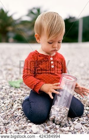 Small Child Sits On His Knees On A Pebble Beach And Holds A Jar Of Pebbles In His Hands