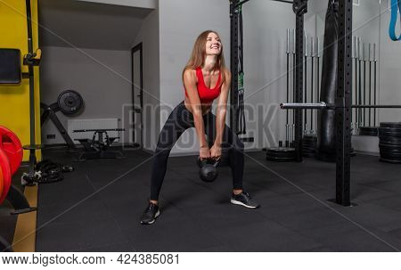 Young Attractive Woman In Sportswear Practices Heavy Kettlebell Exercise In Modern Gym. Free Weights