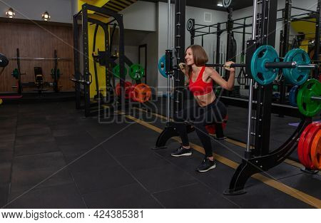 Lovely Fit Woman Practicing Squats In Exercise Machine In The Gym