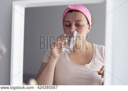 Woman Rinsing Tooth With Water And Brushes Her Teeth In The Bathroom. Oral Hygiene And Teeth Care.