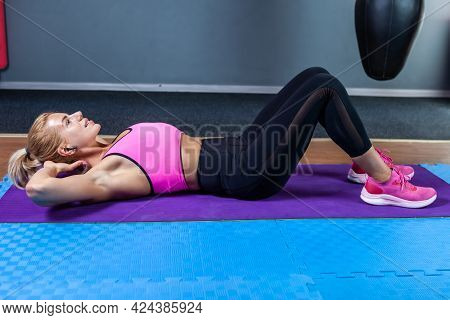 Blond Sport Woman Lying On Mat And Exercising Abdominal Muscles In Gym, Lower-body Workouts. Sports