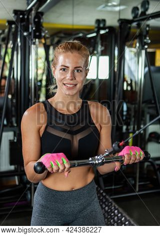 Muscular Blonde Young Woman Doing Exercises For Triceps On Cable Machine At The Gym.