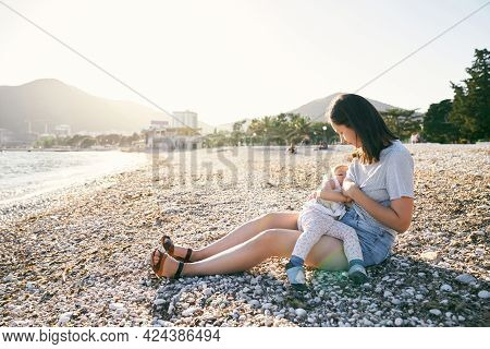 Mom Sits On A Pebble Beach And Breastfeeds A Little Girl