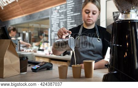 A Barista Prepares A Fresh Latte With Milk In A Cafe. Girl Salesman In Uniform Pours Milk Into Paper