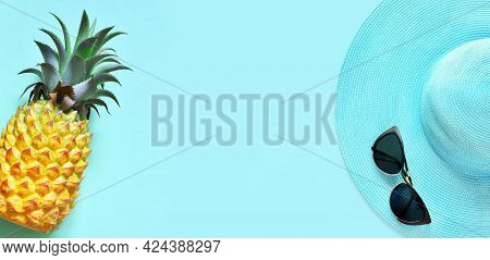 Yellow Pineapple And Blue Hat With Sunglasses On A Blue Background.