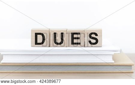 Text Dues On Wooden Cubes On A Stack Of Books On The Table