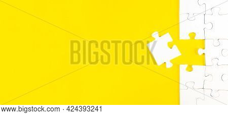 Top View Of Jigsaw Puzzle With One Piece Left On Yellow Background, Completing A Task Or Solving A P