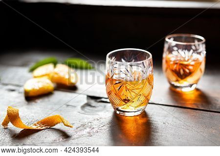 Two Glasses With Tangerine Liqueur On An Old Wooden Background
