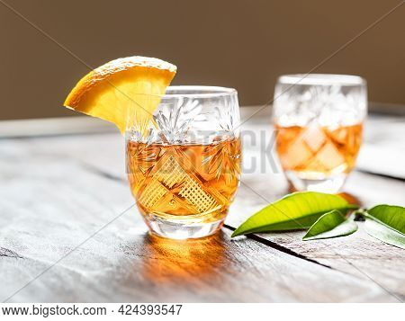 Two Shots With Tangerine Liqueur On An Old Wooden Table