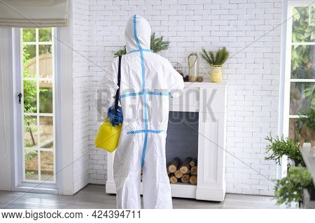 A Medical Staff In Ppe Suit Is Using Disinfectant Spray In Living Room, Covid-19 Protection , Disinf