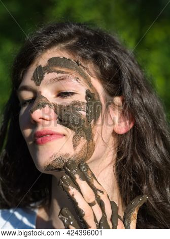 Muddy Face Of A Young Long Haired Brunette Caucasian Woman Outdoors On A Sunny Summer Day