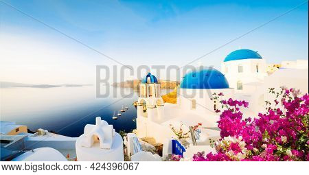 Traditional Greek Village Oia Of Santorini, With Blue Domes Against Sea And Caldera, Greece With Flo