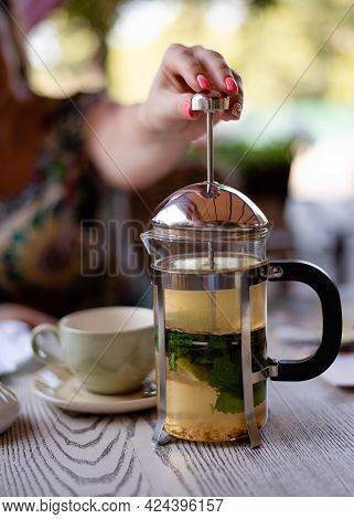 A Woman Pressing The Plunger Of A French Press In The Cafe