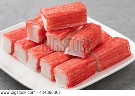 Plate with whole and half red Japanese Surimi sticks close up
