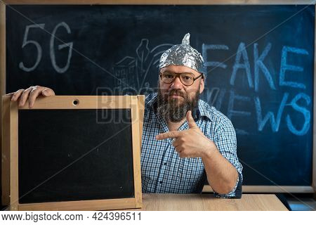 A Strange Guy Conspiracy Theorist In A Protective Aluminum Foil Hat And Glasses Sits At A Table And