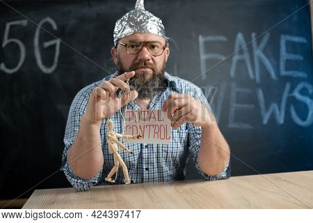 A Conspiracy Theorist In A Foil Hat Controls A Wooden Man And The Inscription Is Total Control. Cons