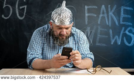 Portrait Of A Crazy Conspiracy Theorist With A Mobile Phone In His Hands And A Protective Cap Made O