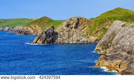Rock Cliffs Jutting Into The Blue Sea In The Cantabrian Sea. Santander.