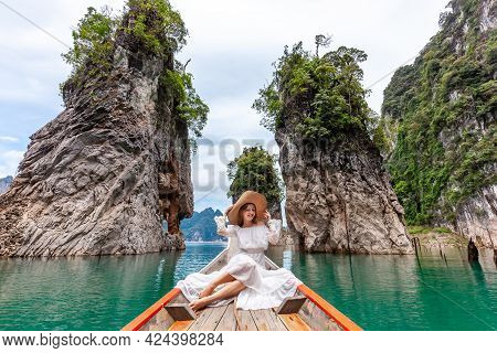 Young Female Tourist In Dress And Hat At Longtail Boat Near Famous Three Rocks With Limestone Cliffs