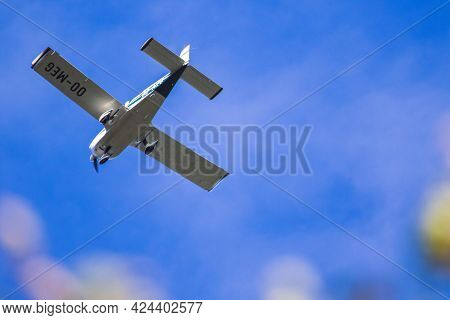 A Portrait Of A Small Sports Airplane Flying Through A Blue Sky, With Some Small Tin Clouds Behind T