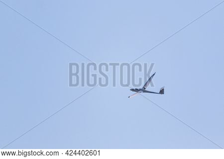 A Portrait Of A Glider Plane Flying In The Distance In A Light Blue Sky. The Plane Is Soaring Throug