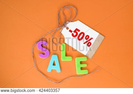 The Word Sale Is Written In Plastic Multicolored Letters On An Orange Background. A Tag For The Pric