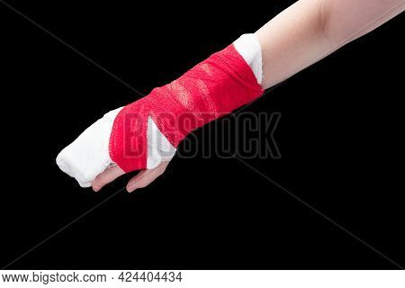 Broken Arm With White Gypsum And Red Bandage Isolated On Black Background