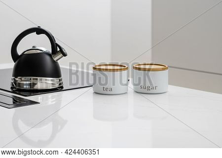 Black Whistle Kettle On Induction Cooktop Built In Glossy Kitchen Counter With Jars Next To It, Gett