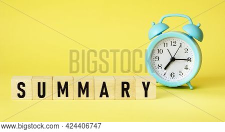 Summary Word On Wooden Cubes Next To Alarm Clock On Yellow Background.