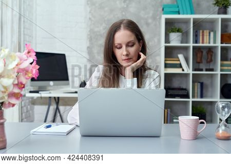 Businesswoman working with laptop computer at office Young woman at home sitting at desk browsing internet, tele working, thinking.