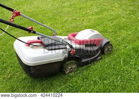 Lawn Mower On A Green Meadow. Gardening Background. Gardening And Landscaping Concept.
