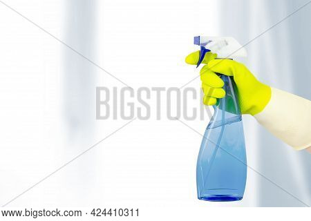 Washing Windows Theme. Top View Of Hand In Yellow Rubber Gloves Holding Cleaning Spray Bottle. Sprin