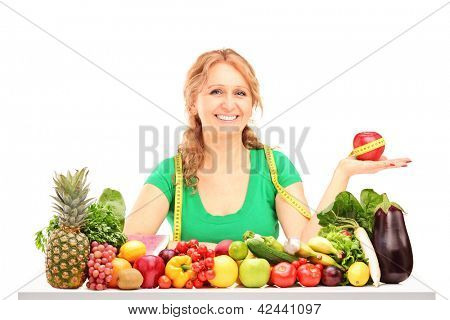 Smiling woman with fruits and vegetables holding an apple with measuring tape isolated on white background