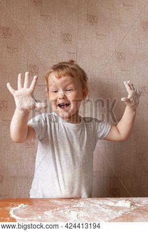Portrait Little Happy Girl Standing Wooden Table Flour, Laughing, Raising Her Hands Soiled Flour. Co