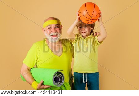 Family Sport. Grandfather With Yoga Mat And Child With Basketball Ball. Grandpa And Grandson Sportin