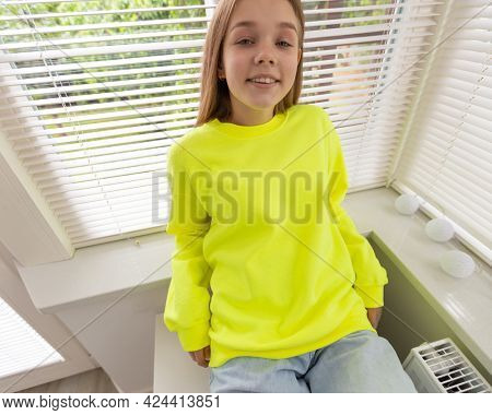 Fashion mockup with teenage girl, whitch is wearing yellow sweatshirt. On blouse is empty space for logo, inscription or design. Girl in casual outfit in home.
